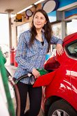 stock photo of petrol  - Woman refuelling a car at a petrol station - JPG