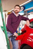 pic of petrol  - Man refuelling a car at a petrol station - JPG