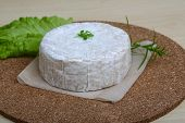 picture of brie cheese  - Brie cheese with salad leaves on the wood background - JPG