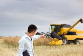 stock photo of combine  - Young businessman pointing finger into combine harvester during harvest - JPG
