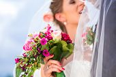 stock photo of bridal veil  - Bridal pair kissing under veil at wedding - JPG