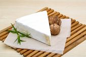 stock photo of brie cheese  - Brie cheese with wallnut and terragon on wood background - JPG