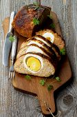 image of meatloaf  - Delicious Homemade Meatloaf Stuffed with Boiled Eggs on Cutting Board with Knife and Fork closeup on Rustic Wooden background - JPG