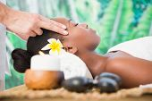 foto of day care center  - Side view of an attractive young woman receiving temple massage at spa center - JPG
