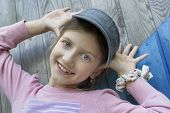 stock photo of tilt  - Little girl of 7 making face with hands up tilted outdoor shot - JPG