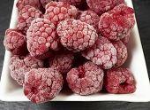 stock photo of fruit platter  - Macro shot of some frozen raspberries in a white porcelain dish on a slate platter - JPG
