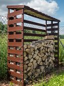 picture of firewood  - Woodshed with arranged chopped firewood - JPG