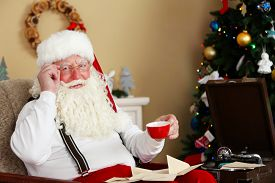 picture of letters to santa claus  - Santa Claus sitting with children letters in comfortable chair near fireplace at home - JPG
