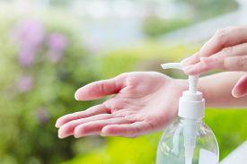 image of gels  - Female hands using wash hand sanitizer gel pump dispenser - JPG