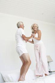 image of pyjama  - Senior Couple Jumping On Bed Wearing Pyjamas - JPG