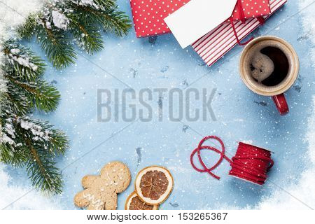 Christmas background with gift boxes, coffee and fir tree on stone table. Top view with copy space.