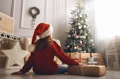 Merry Christmas and Happy Holidays! Cheerful cute little child girl with present. Kid holds a gift b poster