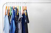 Clothes hanging on rack, closeup poster
