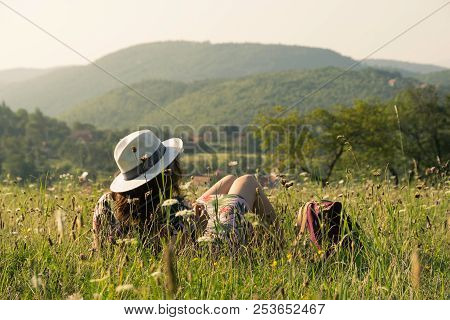 poster of Woman on vacation relaxing in fields. Summer vacation. Young woman traveler in vacation in nature. Traveler in vacation with backpack in nature. Girl traveler relaxes in fields in vacation. Traveler. Vacation . Backpack. Woman. Nature. Healthy lifestyle