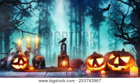 poster of Scary horror background with halloween pumpkins jack o lantern, placed on wooden deck. Halloween spo