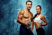 stock photo of muscle man  - Athletic man and woman with a dumbells - JPG