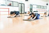 Determined Young Women And Man Doing Yoga On Exercise Mats In Gym poster