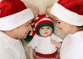 Happy Couple With Baby In Christmas Hats On Fuzzy Rug, Top View poster