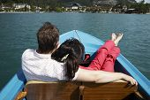 stock photo of flatboat  - young couple boating on the lake in Austria - JPG