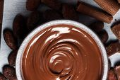 Melting Chocolate  Or Melted Chocolate With A Chocolate Swirl. Many Stack And Chips With Powder. poster