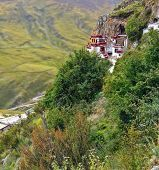Tibetan Drak Yerpa Buddhist Monastery On The Cliff In Mountains Of Tibet. The Holiest Caves For Medi poster