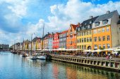 People Walking At Sunny Nyhavn Embankment With Moored Boats, Copenhagen, Denmark poster