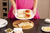 Woman Holding A Plate With Sandwiches Ready For Heating In A Sandwich Maker; Woman Making Hot Sandwi poster