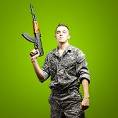 portrait of young soldier holding rifle wearing urban camouflage over green background