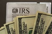 image of irs  - hundred dollar bills fanned out over an IRS envelope metaphor for paying taxes or getting a refund - JPG