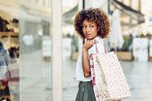Young Black Woman In Front Of A Shop Window In A Shopping Street. African Girl With Afro Hairstyle W poster