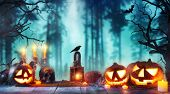 Scary horror background with halloween pumpkins jack o lantern, placed on wooden deck. Halloween spo poster