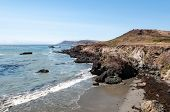 A Rocky Calfornia Coastline With Fog Shrouding The Hills In The Distance. poster
