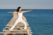stock photo of tai-chi  - attractive woman doing tai chi or yoga stretching exercises at the beach - JPG