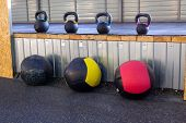 Iron Dumbbells Of Different Weights With Multi-colored Handles Stand In The Gym On A Rubber Mat. Med poster