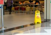 Yellow Plastic Cone With Sign Showing Warning Of Wet Floor In Restaurant In Department Store poster