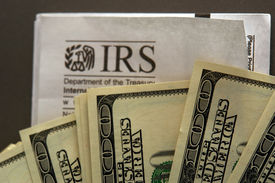 foto of irs  - hundred dollar bills fanned out over an IRS envelope metaphor for paying taxes or getting a refund - JPG