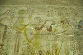 pic of pharaoh  - Ancient Egyptian bas relief carving showing the Pharaoh Seti I offering incense to the god of the underworld Osiris with the goddess Hathor standing behind him.  