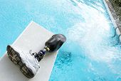foto of artificial limb  - Cannonball splash in a pool with prosthetic leg left on diving board - JPG