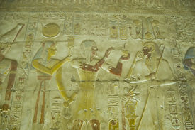 pic of underworld  - Ancient Egyptian bas relief carving showing the Pharaoh Seti I offering incense to the god of the underworld Osiris with the goddess Hathor standing behind him.  