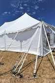 Straps Hold Up A White Tent In A Field