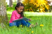 stock photo of black american  - Outdoor portrait of a cute young black little girl reading a book  - JPG