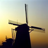 Sunrise Behind A Group Of Traditional Dutch Windmills