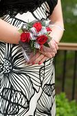 pic of night gown  - Red rose wrist corsage displayed on the crossed - JPG