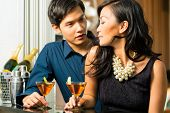 stock photo of minx  - Asian man and woman in flirting intimately at bar drinking cocktails - JPG