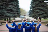 stock photo of tassels  - Backs of ecstatic students in graduation gowns holding diplomas - JPG