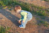 pic of girlie  - little child in the jeans coverall pick up stones on the dirt road - JPG