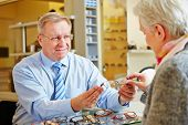 Optician giving consultation to senior woman for new glasses