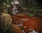 picture of grotto  - A small waterfall cascades over mossy rocks in a beautiful stone grotto - JPG