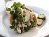 stock photo of souvlaki  - Chicken pita Greek style gyro sandwich served in silver foil on plate - JPG