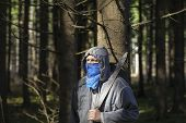 foto of machete  - Man with a machete in the woods leaning against tree - JPG